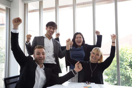 Successful startup entrepreneurs and business people team achieving goals celebrating giving high five in office. Success and winning concept