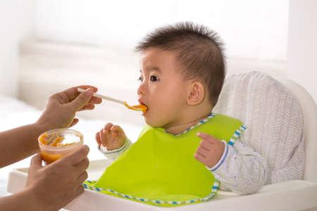 Maman donne de la nourriture liquide à son fils asiatique