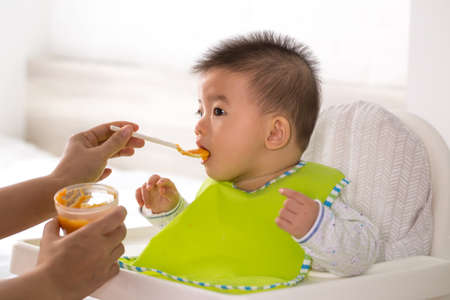 Mom is feeding liquid food to her Asian son Stockfoto - 123083314