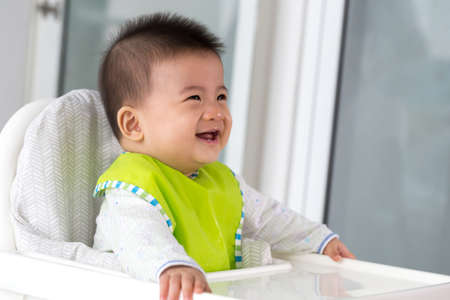 Fröhliches, glückliches asiatisches Baby, das darauf wartet, Essen zu essen und auf einem Kinderstuhl zu sitzen? Standard-Bild