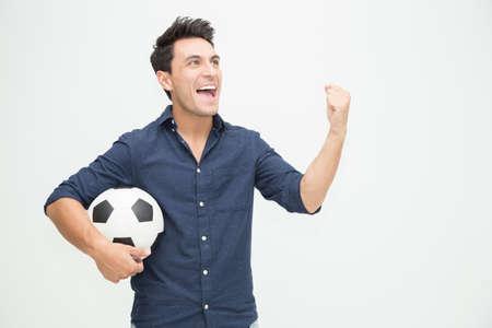 Jeune homme caucasien tenant le football et célébrant avec amusement isolé sur fond blanc, concept de fans de football enthousiastes et excités