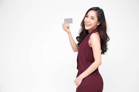 Donna asiatica che presenta la carta di credito in mano per effettuare acquisti di pagamento isolati su sfondo bianco
