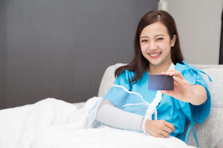 Asian woman holding insurance cards and wear patient suits on the arms wearing soft splint sitting on bed at hospital