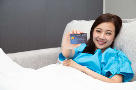 Young Asian beautiful woman patient showing credit card and sitting on bed at hospital, Insurance policy by bank concept Stock Photo