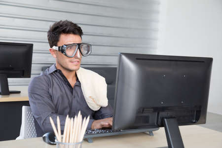 Businessman wearing diving glasses or snorkeling mask during working with computer in the office, Summer vacation plan and long holiday concept