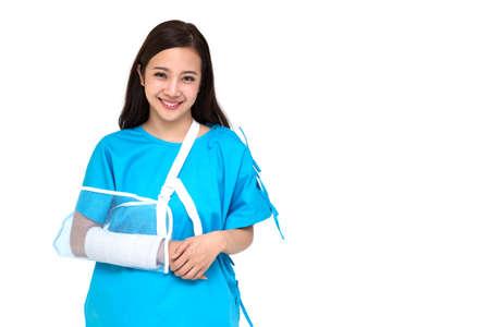 Jeune belle femme asiatique portant des tenues de patient et portant une attelle douce en raison d'un bras cassé isolé sur fond blanc, concept d'accident personnel