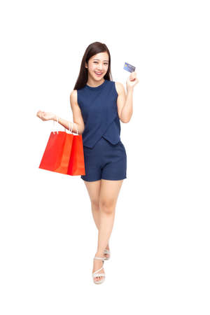 Happy Asian woman holding credit card or cash advances and shopping bag, Pay instead of money and specially curated benefits for lady card concept