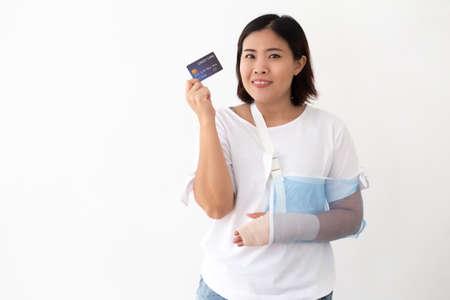Asian woman holding credit card and put on a soft splint due to a broken arm isolated on white background, Personal accident concept Reklamní fotografie