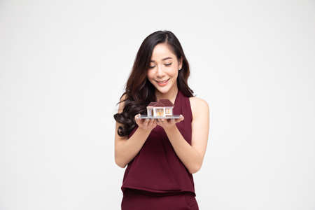 Happy Asian woman holding home model, Planning to take on a large loan for purchase house concept