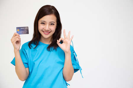 Young Asian beautiful woman patient showing credit card and ok sign isolated on white background, Insurance policy by bank concept