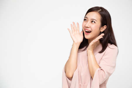 Portrait of excited screaming young asian woman standing in red dress isolated over white background, Wow and surprised business woman concept Banco de Imagens