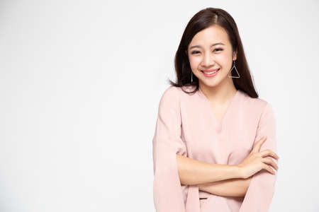 Portrait of successful business asian women in pink dress with arms crossed and smile isolated over white background, Young businesswoman smiling and looking at camera, Happy feeling concept Stock Photo
