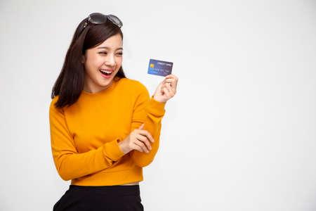 Fröhliche asiatische Frau in gelbem Hemd mit Kreditkarte oder Barvorschuss, Bezahlen statt Geld und speziell kuratierten Vorteilen für das Kartenkonzept der Dame