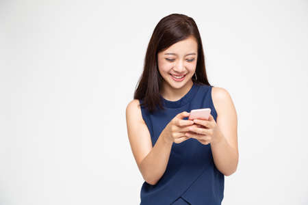Cheerful young Asian woman using smartphone and receiving good news from the message on mobile chat application over white background
