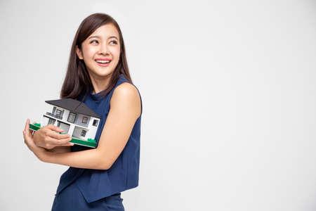 Joven mujer asiática sonriendo y abrazando el modelo de muestra de casa de ensueño aislado sobre fondo blanco, concepto de seguro de hogar y bienes raíces