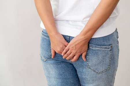 Woman wearing of jean pants from back, Female bottom and hemorrhoid symptoms from rectal cancer concept