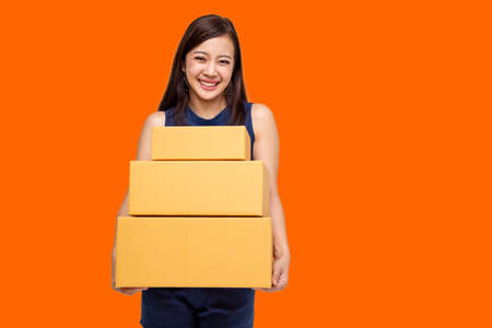 Happy Asian woman holding package parcel box on orange background, Delivery courier and shipping service concept