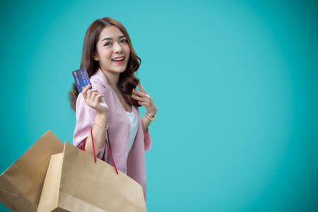 Asian woman using a credit card and enjoys shopping isolated on blue background