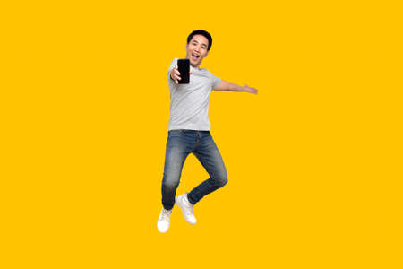 Asian man jumping and presenting mobile phone isolated on yellow background 版權商用圖片