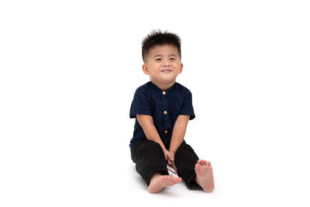 Portrait of a Asian baby boy sitting on floor looking shy and smiling isolated on a white background, 1 year 10 month old