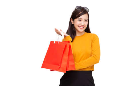 Portrait of a happy young woman holding shopping bags isolated over white background, Year end sale or mid year sale promotion clearance for Shopaholic concept, Asian female model