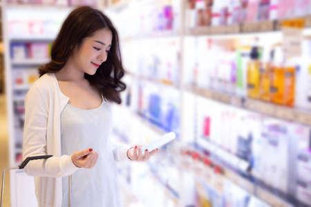 Young Asian woman choosing cosmetic cream in beauty shop