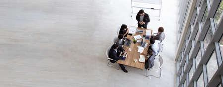 Draufsicht auf eine Gruppe multiethnischer beschäftigter Menschen, die in einem Büro arbeiten, Luftbild mit Geschäftsmann und Geschäftsfrau, die um einen Konferenztisch mit leerem Kopienraum sitzen, Geschäftstreffenkonzept Standard-Bild