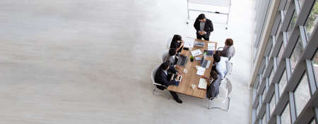 Top view of group of multiethnic busy people working in an office, Aerial view with businessman and businesswoman sitting around a conference table with blank copy space, Business meeting concept Stock Photo