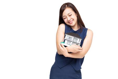 Jeune femme asiatique souriante et étreignant le modèle d'échantillon de maison de rêve isolé sur fond blanc, concept immobilier et assurance habitation