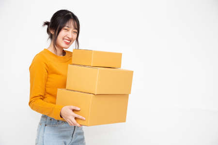 Happy Asian woman holding package parcel box on white background, Delivery courier and shipping service concept Stock Photo
