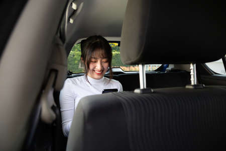 Asian teenager woman using a smartphone in back seat of car, Passengers use an app to order a ride and Peer-to-peer ride sharing concept Banque d'images