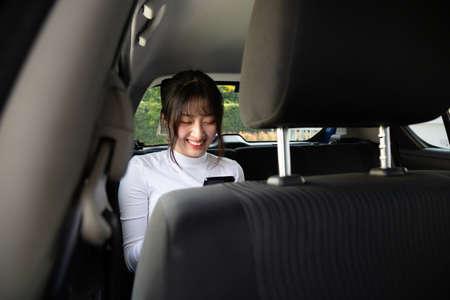 Mujer adolescente asiática que usa un teléfono inteligente en el asiento trasero del automóvil, los pasajeros usan una aplicación para solicitar un viaje y el concepto de intercambio de viaje entre pares