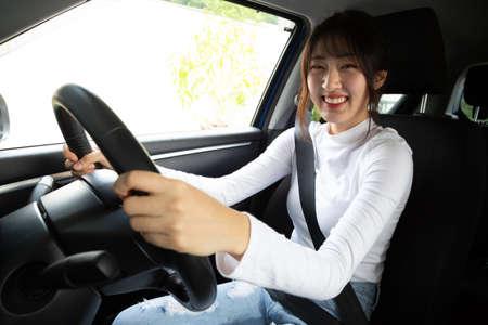 Asian women driving a car and smile happily with glad positive expression during the drive to travel journey, People enjoy laughing transport and relaxed happy woman on road trip vacation concept