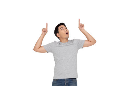 Portrait of a happy Asian young man pointing fingers up at copy space isolated over white background
