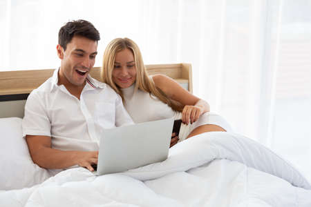 Caucasian couple searching cheap flight ticket and hotel in web online with laptop on bed, Preparing and find amazing accommodations for holidays concept Archivio Fotografico - 131279818
