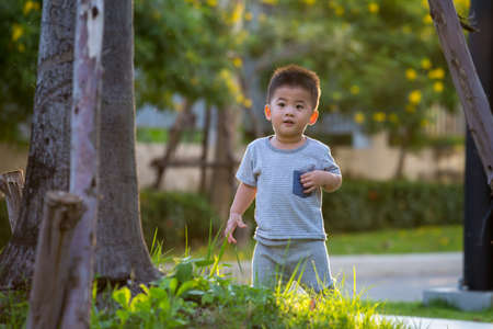 Asian baby boy running in the garden during the evening, with the sun shining from the back of the child