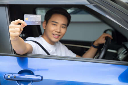 Happy young Asian man holding payment card or credit card and used to pay for gasoline, diesel, and other fuels at gas stations, Driver with fleet cards for refueling car