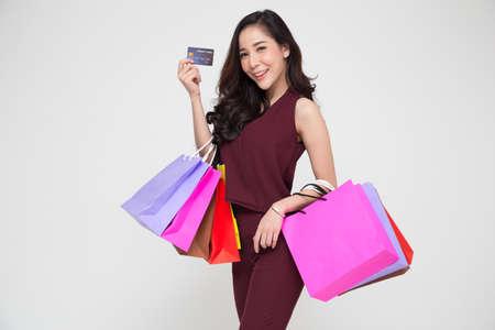 Porträt einer glücklichen jungen asiatischen Frau in rotem Kleid, die Einkaufstaschen und Kreditkarte einzeln auf weißem Hintergrund hält, Jahresendverkauf oder Verkaufsförderungsfreigabe zur Jahresmitte für Shopaholic-Konzept Standard-Bild