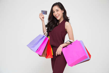 Portrait of a happy young Asian women in red dress holding shopping bags and credit card isolated over white background, Year end sale or mid year sale promotion clearance for Shopaholic concept