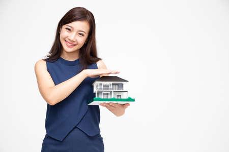 Portret van mooie jonge Aziatische vrouw met handen die huis of huismodel beschermen dat op witte achtergrond, onroerend goed en huisverzekeringsconcept wordt geïsoleerd Stockfoto