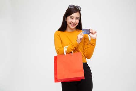 Portret szczęśliwej młodej kobiety trzymającej torby na zakupy i kartę kredytową na białym tle nad białym tłem, sprzedaż na koniec roku lub wyprzedaż w połowie roku dla koncepcji zakupoholiczki, azjatycka modelka Zdjęcie Seryjne