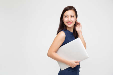 Happy carefree young Asian woman dancing and listening to music top chart playlist from smartphone in bag over white background