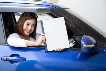 Happy Asian woman holding car insurance document book and sitting in car, Safety vehicle and protection client person concept