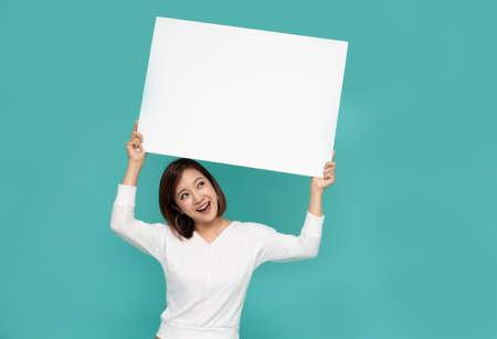 Joven y atractiva mujer asiática mostrando y sosteniendo la pizarra en blanco, mostrando la placa vacía para ingresar su texto Foto de archivo