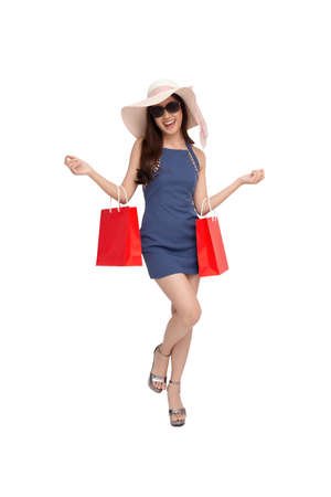 Portrait of a happy young woman holding red shopping bags isolated over white background, Year end sale or mid year sale promotion clearance for Shopaholic concept, Asian female model