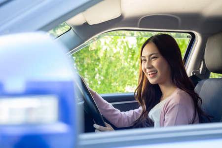 Donna asiatica che guida un'auto e sorride felicemente con felice espressione positiva durante il viaggio in auto, le persone si divertono a ridere del trasporto e rilassata donna felice sul concetto di vacanza su strada