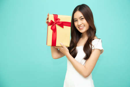 Happy beautiful asian woman smile with gold gift box isolated on light green background. Teenage girls in love, Receiving gifts from lovers. New Year, Christmas and Valentines Day concept Stock Photo