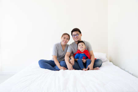 Asian father, mother and son are playing superhero on the bed at bedroom. Friendly family having fun Archivio Fotografico - 140882215