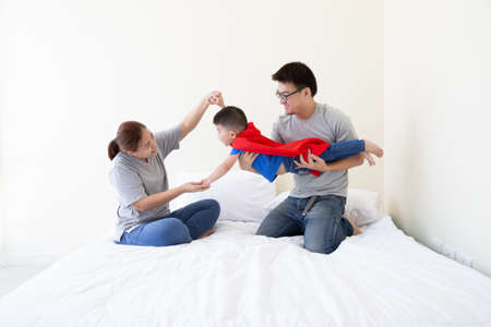 Asian father, mother and son are playing superhero on the bed at bedroom. Friendly family having fun Archivio Fotografico - 140882213