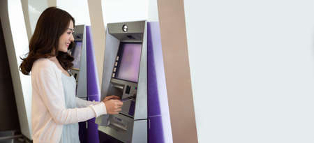 Young Asian woman withdrawing money with a card at the automatic machine, Female standing at ATM of the bank